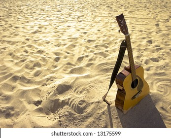 An acoustic guitar standing in the sandy beach.
