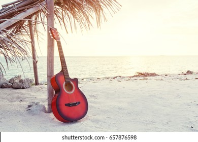 An acoustic guitar standing at the sandy beach under palm tree