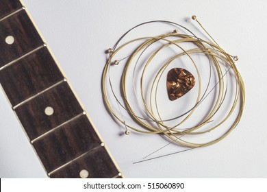 Acoustic guitar strings, pick and guitar neck on gray paper background