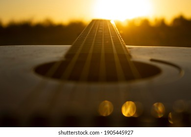Acoustic guitar with the sunset.The guitar's chords were chosen to be the leading lines that lead people's eyes straight to the sunset.