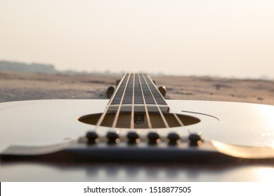 Acoustic guitar with sunset sky