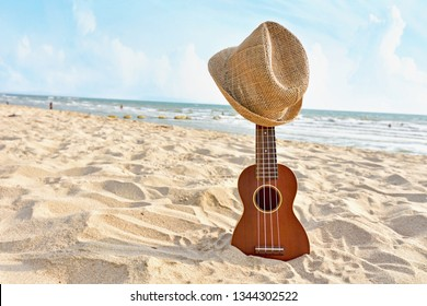 An acoustic guitar ukulele standing in the sandy beach with hat