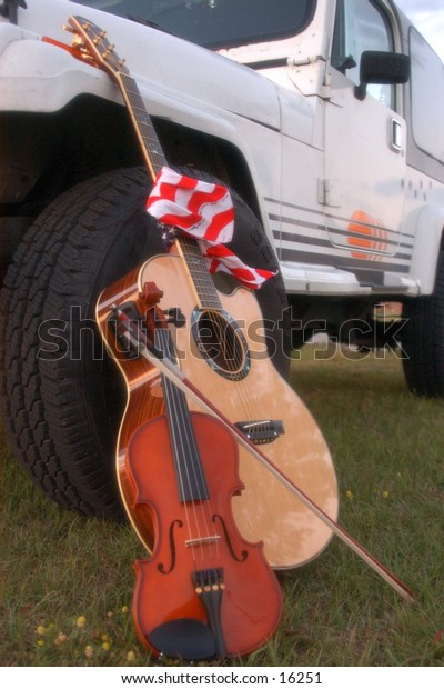 Acoustic Guitar Violin and American Flag beside Jeep Wrangler