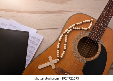 Acoustic guitar with wooden cross and songbook with religious scores on wooden table close up. Top view. Horizontal composition.