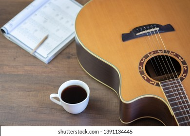 Acoustic guitar and Write musical notes and cup of coffee on table wooden background