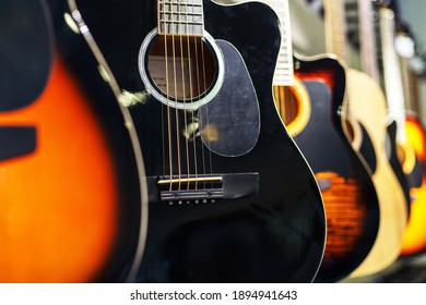 Acoustic guitars of different types and colors are hanging in the musical instrument store. Close-up
