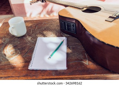 Acoustic guitars with a notebook and a cup of water on table bac