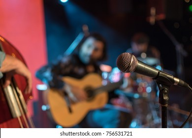 Acoustic trio band performing on a stage in a nightclub, with the microphone in focus waiting for its singer