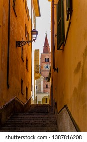 ACQUI TERME, ALESSANDRIA, PIEDMONT, ITALY - June 3, 2018: View of an alley with steps and on the bottom the bell tower of the Cathedral of Santa Maria Assunta in the historic center.