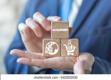 Acquiring online internet marketing business concept on a wooden blocks in a buinessman hands. Acquire technology payment banking service.