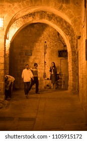 Acre, Israel - December 20 2017: People walking along the narrow alleyway in the Old City Acre, an ancient port city.