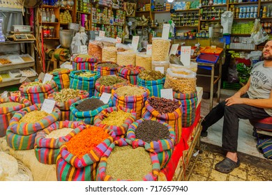 ACRE, ISRAEL - SEPTEMBER 18, 2017: Various spices in colorful sacks on sale in the market, with a seller, in Acre (Akko), Israel