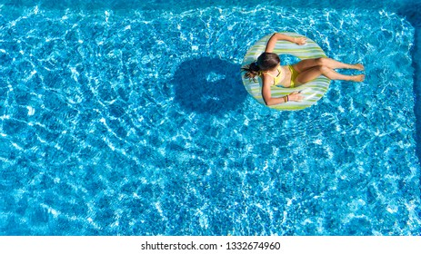 Acrive girl in swimming pool aerial top view from above, kid swims on inflatable ring donut , child has fun in blue water on family vacation resort