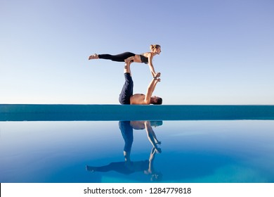 Acro yoga concept. Pair yoga. Couple of young sporty people practicing yoga lesson with partner, man and woman in yogi exercise, arm balance pose, working out by pool, above beach, against blue sky