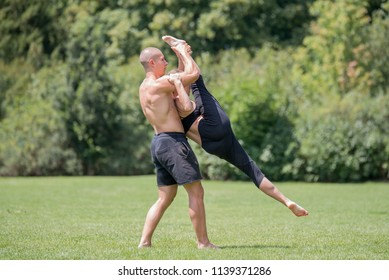 Acro yoga, two sporty people practice workout in pair, couple doing stretching exercise in the nature.