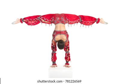 Acrobat does gymnastic exercises , the isolated image on a white background. Young athletic woman in a red leotard, practicing acrobatics.