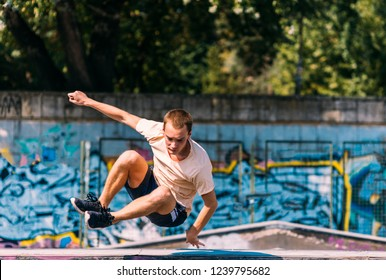 Acrobat man training parkour exercise while jumping obstacles