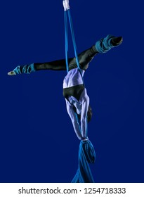 Acrobat on the fabric on a blue background. The figure in the blue color. Gymnast in the air. Athlete and exercises. Sport.