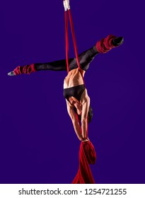Acrobat on the fabric on a blue background. Gymnast in the air. Athlete and exercises. Sport. Master of circus art.