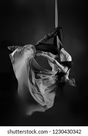 Acrobat on the fabric on a dark background. Gymnast in the air. Athlete and exercises. Sport. Monochrome image.