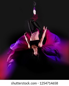 Acrobat on the fabric on a dark background. Gymnast in the air. Athlete and exercises. Sport.
