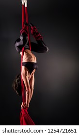 Acrobat on the fabric on a dark background.  Gymnast in the air.  Athlete and exercises. Sport. Master of circus art.