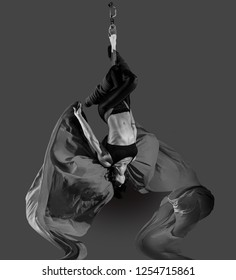 Acrobat on the fabric on a dark background.Gymnast in the air. Athlete and exercises. Sport. Monochrome image.