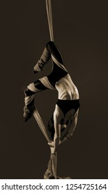 Acrobat on the fabric on a gray background. Gymnast in the air. Athlete and exercises. Monochrome image. Sport. Master of circus art. Sepia.