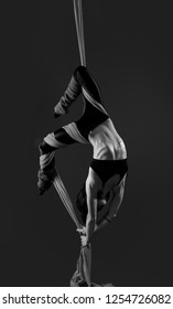 Acrobat on the fabric on a gray background. Gymnast in the air. Athlete and exercises. Monochrome image. Sport. Master of circus art.