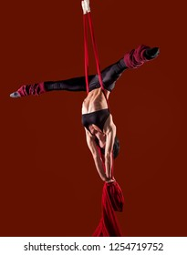 Acrobat on the fabric on a red background. Gymnast in the air. Athlete and exercises. Sport.