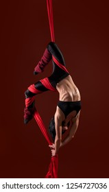 Acrobat on the fabric on a red background. Gymnast in the air. Athlete and exercises.  Sport. Master of circus art.