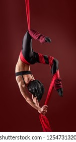 Acrobat on the fabric on a red background. Gymnast in the air. Athlete and exercises.Sport. Master of circus art.