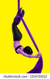 Acrobat on the fabric on a yellow background. Gymnast in the air. Athlete and exercises. Purple colored figure on a yellow background. Sport.