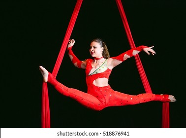 Acrobat performs a difficult trick in the circus.
