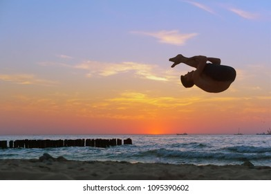acrobat at sunset of the sea coast, somersault on the beach, acrobatics on the sea