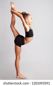 Acrobatic choreography concept. Full length profile portrait of smiling young little gymnast showing her skills on gray background. Studio shot