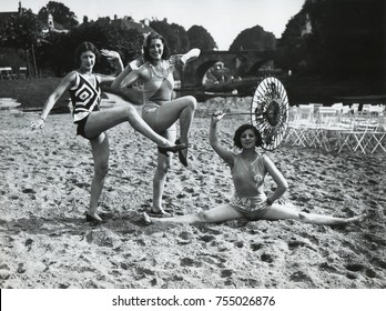 Acrobatic French women pose in the latest fashionable bathing suits on the sand beach at Dieppe. Ca. 1925.