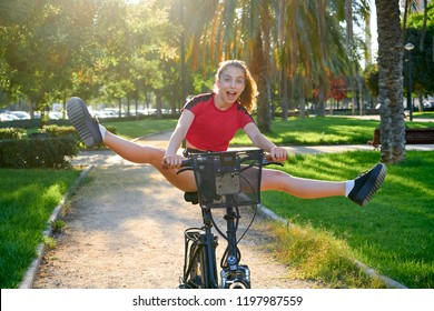 Acrobatic girl riding e-bike in a city park with red t-shirt foldable ebike