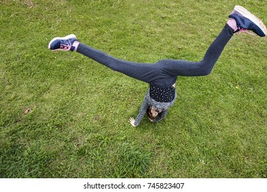 Acrobatic teenage girl doing a cartwheel excercise while having fun outdoor on the green grass with a view from above