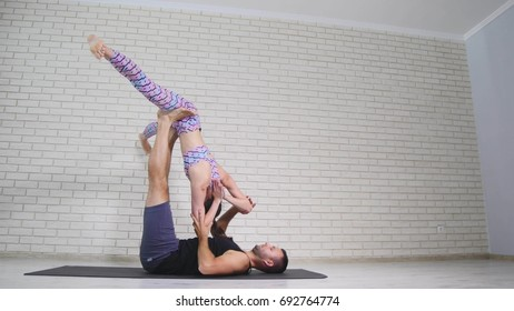 Acrobatic yoga. Young woman and man performing exercises. The combination of acrobatics and yoga.