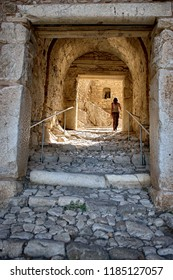 ACROCORINTH, GREECE - JULY 12, 2009: woman crosses stone entrance Acropolis Ancient Corinth