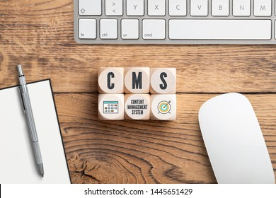 acronym CMS on cubes in front of a computer keyboard