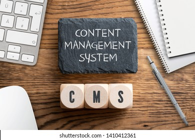 "acronym CMS on wooden cubes and writing slate with explanation ""Content Management System"" on wooden background"