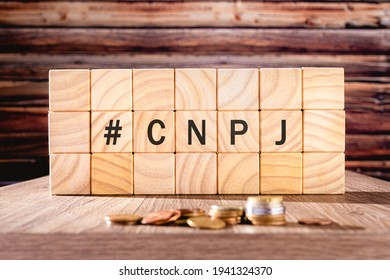 Acronym CNPJ written with black letters on wooden cubes grouped as a wall.