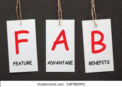 Acronym FAB - Feature Advantage Benefits written on paper labels set on black background. Business concept