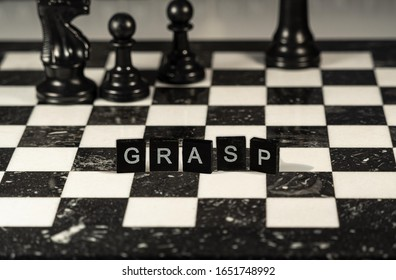 the acronym grasp for General Responsibility Assignment Software Patterns concept represented by wooden letter tiles