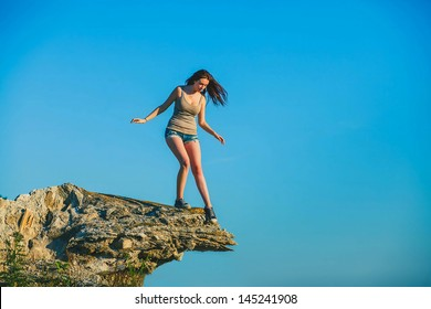 acrophobia woman tall stands on top of a rock cliff edge and is fearful horror