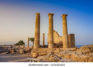 The Acropolis of Lindos in Rhodes, Greece at sunset. Scenic view of Doric columns from the ancient Temple of Athena Lindia setting sun light above the columns. Rhodes, Dodecanese, Greece, Europe