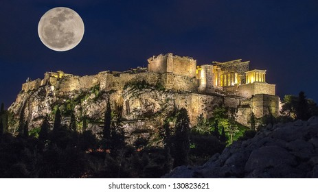 Acropolis in the moonlight. Night. The full moon and the light of lanterns light up the Acropolis. The trees in the background and lighting. In the foreground is the ancient stones in the moonlight.