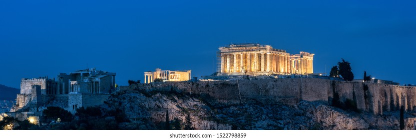 Acropolis at night, Athens, Greece. Famous Parthenon temple is a top landmark of Athens. Panoramic view of Ancient Greek ruins at dusk. Landscape of old Athens city in evening.